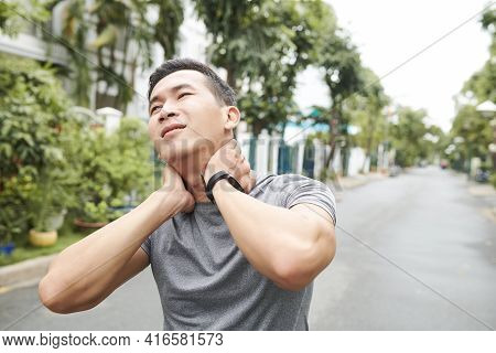 Young Asian Sportsman Suffering From Pain In His Neck, He Is Massaging Neck To Get Relief