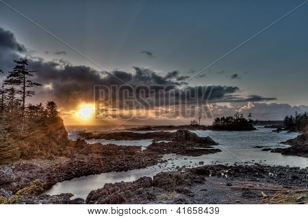 Sun Peaking Through Clouds In Front Of Islands Along Coast