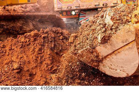 Backhoe Working By Digging Soil At Construction Site. Bucket Of Backhoe Digging Dirt Soil. Excavator