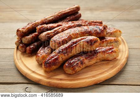 Grilled Sausages On Wooden Board On Grey Background. Top View