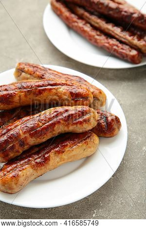 Grilled Sausages On Plate On Grey Background. Top View