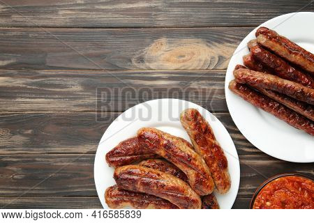 Grilled Sausages On Plate On Brown Wooden Background. Top View