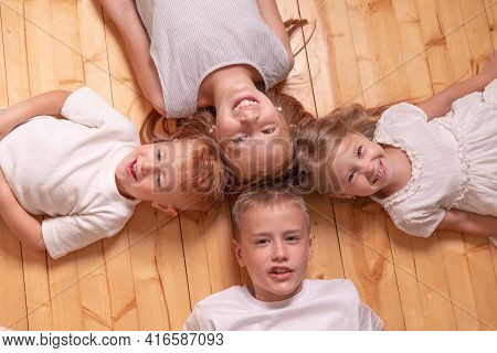 Four Children Lie On The Floor And Looking At Camera. Red Children