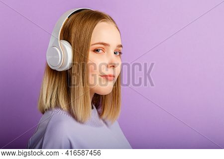 Confident Young woman in headphones portrait. Beautiful serious woman with blonde hairstyle enjoy listen song music in headphone isolated over purple color background. Copy space.