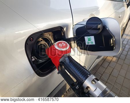 Filling The Car With Gasoline. Insert The Red Gun Into The Tank Of The Car For Refueling. The Proces