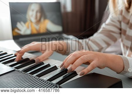 Woman Playing Piano During Video Call Via Laptop. Female Hands Musician Pianist Improves Skills Play