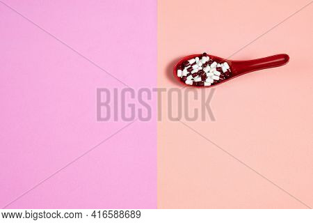 Pharmaceutical Medicine Pill Capsules, In Plastic Red Spoon On Colorful Background.