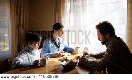 Portrait Of Poor Sad Small Girl With Parents Eating Indoors At Home, Poverty Concept.