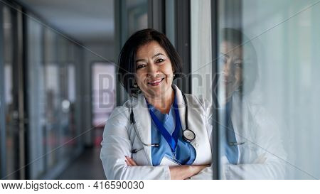 Portrait Of Senior Woman Doctor Standing In Hospital, Looking At Camera.