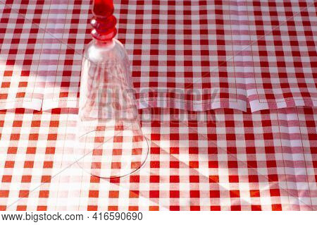 A Glass On A Red - White Checkered Tablecloth