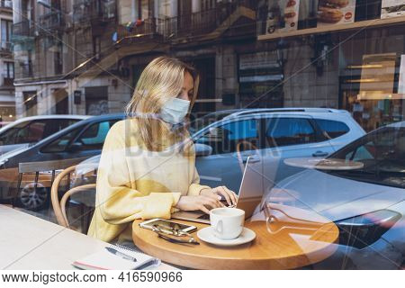 Young Blond Woman With A Face Medical Mask Working At A Laptop In Cafe.