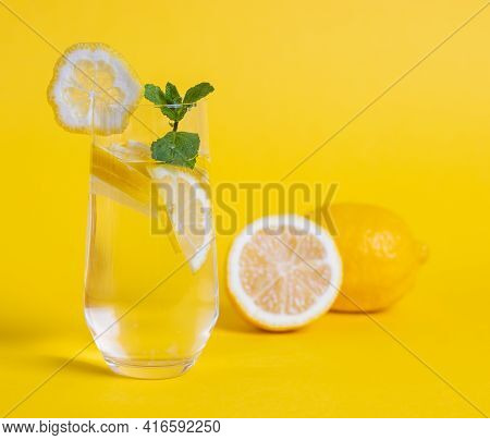 Glass Of Detox Water With Lemon Slices And Mint Leave On Yellow Background. Detoxification Concept
