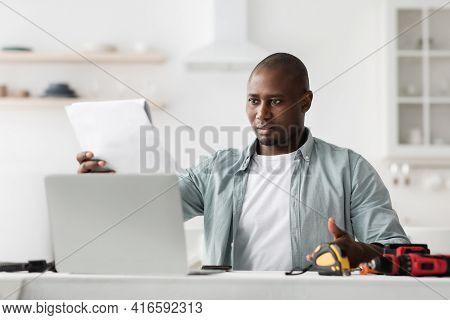 Incorrect Order And Problems In Furniture Assembly. Black Man Comparing Specification With Online Ma