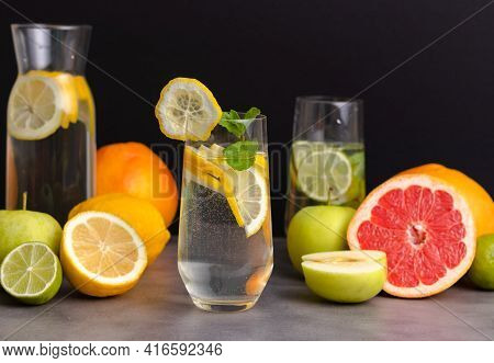 Glass Of Detox Water With Lemon Slices And Mint Leave. Closeup Of Fresh Fruits Prepared For Detoxifi