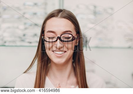 Young Beautiful Model Woman With Glasses For Makeup In Optician. Smiling Woman In Eye Glasses For Ma