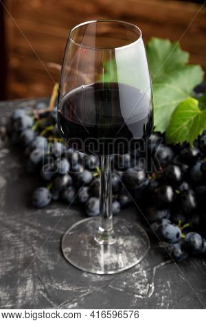 Wine Glass With Red Wine On Black Table, Dark Wooden Background. Red Wine Drink In Glass With Black