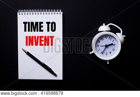 Time To Invent Is Written In A White Notepad Near A White Alarm Clock On A Black Background.