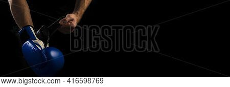 A Man Puts On A Blue Boxing Boxing Glove Before A Boxing Fight On A Black Background