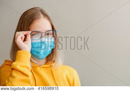 Foggy Glasses Wearing On Young Woman. Teenager Girl In Blue Medical Protective Face Mask And Eyeglas