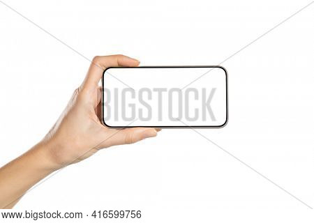 Female hand holding mobile smart phone with blank screen. Hand holding smartphone screen horizontally against white background. Close up of woman hand holding cellphone isolated on white background.