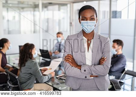 Successful black entrepreneur in conference room leaning over table wearing surgical mask with business people working in background. Portrait of african american leader woman looking at camera.