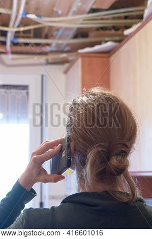 Rear View Of A Worried Woman Calling Home Insurance Because The Kitchen Ceiling Has Collapsed. Home