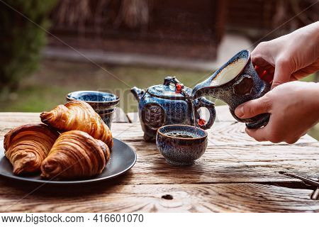 Breakfast With Chinese Tea And Fresh Pastries, Aromatic Butter Croissants. Women's Hands Pour Tea. T