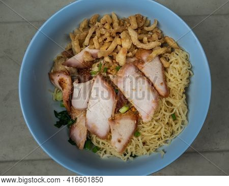 Egg Noodle With Sliced Red Roasted Pork And Wonton, Streaky Pork With Crispy Crackling In Blue Bowl.