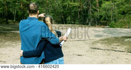 Young Couple Choose A Plot Of Land For Dream House Construction In Forest. Copy Space