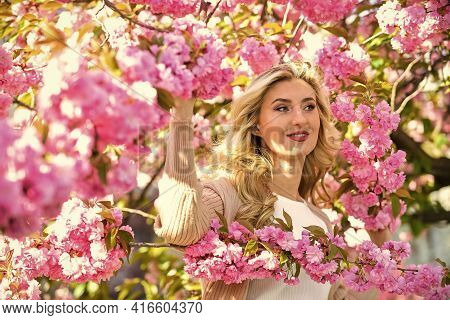Spring Nature. Female Flower Perfume. Pink Flowers Surrounding Her. Cute Woman Makeup Face Blonde Ha