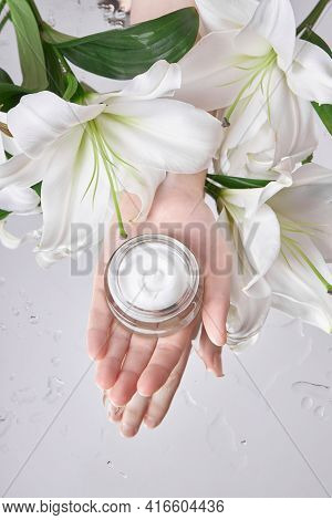 Beauty Jar Cream Hand Cosmetic Woman With Lily Flowers Lie On Table, Jar Cream Product In Hand Woman