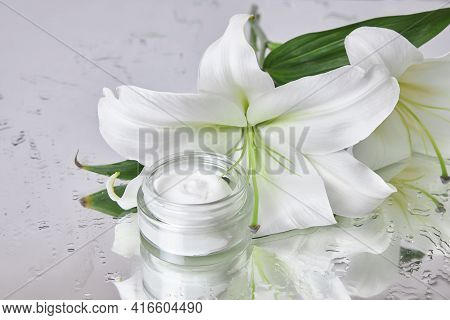 Beauty Jar Cream Cosmetic With Lily Flowers Lie On Table, Jar Cream Product On Wet Flower Mirror Moi