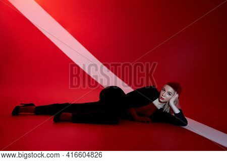 Woman Lies On Red Background With Ray Of Light On Face. Sexy Nude And Confident Blonde Woman In Blac