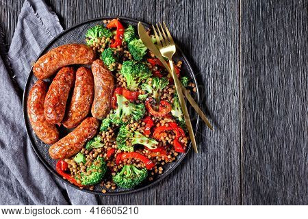 Italian Pork Sausages Braised With Brown Lentils, Red Pepper, And Broccoli On A Black Plate On A Dar