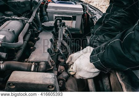 Replacing High-voltage Wires On A Car Engine. Man Mechanic Repairing An Old Vehicle Is In Service. O