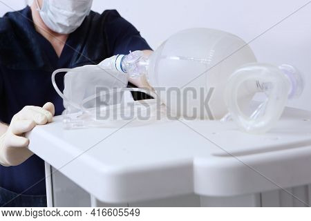 The Anesthesiologist Moves The Device For Artificial Ventilation Of The Lungs.ambu Bag. An Unrecogni