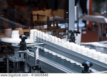 White Plastic Bottle On Capsule Filling Machine Conveyor Belt In Production Line. Pharmaceutical Ind