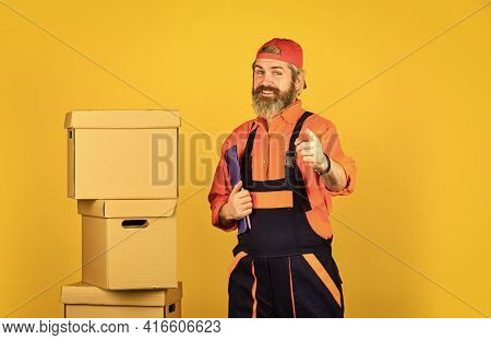 I Can Help You. New House At Moving Day. Bearded Man Builder In Boilersuit Hold Boxes. Moving To New