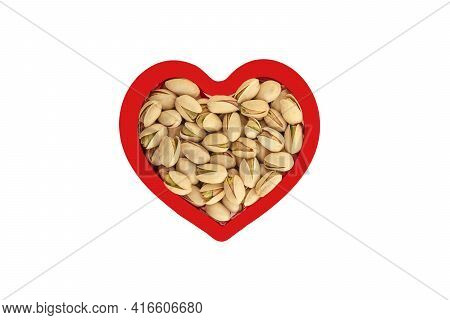 Heap Of Pistachio In Heart Shape Red Frame Isolated On White.
