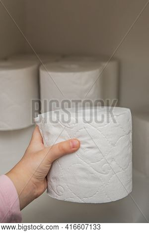 Roll Of White Toilet Paper In Hand. The Childs Hand Takes A Roll Of Toilet Paper From The Cabinet. L