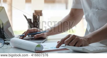 Man Accountant Analyzing Financial Graph Data With Calculator