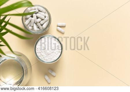 Collagen Powder, Tablets And A Glass Of Water On A Beige Background With A Copy Space. Extra Protein