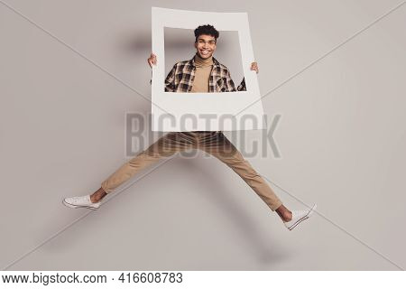 Full Size Photo Of Dark Skin Handsome Man Jump Wear Casual Clothes Hold Frame Isolated On Grey Color