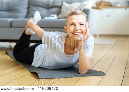 Happy Smiling Senior Woman Stretching And Looking To Camera. Exercise For Physical Health. Wellness