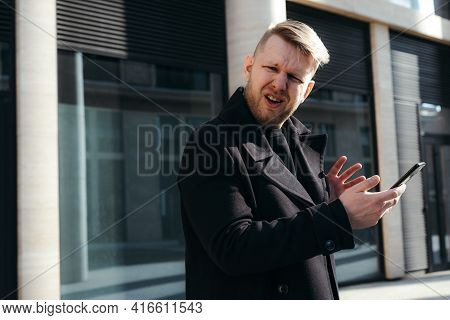 Stylish Businessman In A Black Coat Holds A Phone In His Hands And Is Perplexed And Disappointed Loo