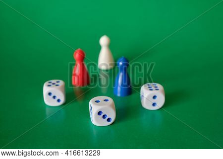 Dice And Game Pieces Of Different Colors. Collection Of Dice Cubes On Green Table.