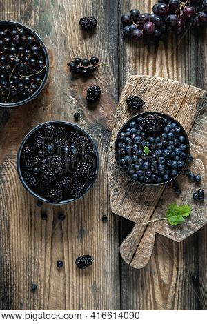 Blueberry, Blackberry, Blackcurrant In Bowls On A Wooden Background. Flat Lay, Top View.