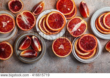 Sliced Sicilian Bloody Oranges In Difference Ceramic Plates On A Grey Background. Top View. Flat Lay