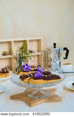 Dessert, Choux Pastry Sweets With Vanilla Custard, Covered With Chocolate Glaze, On A Glass Stand On