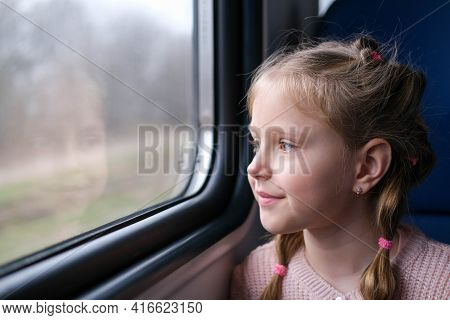 The Child Is On The Train And Looks Out The Window. A Little Girl Travels In A Train.